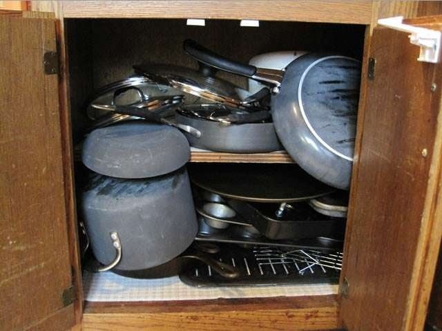 Picture showing overloaded cupboard with pots and pans with handles
